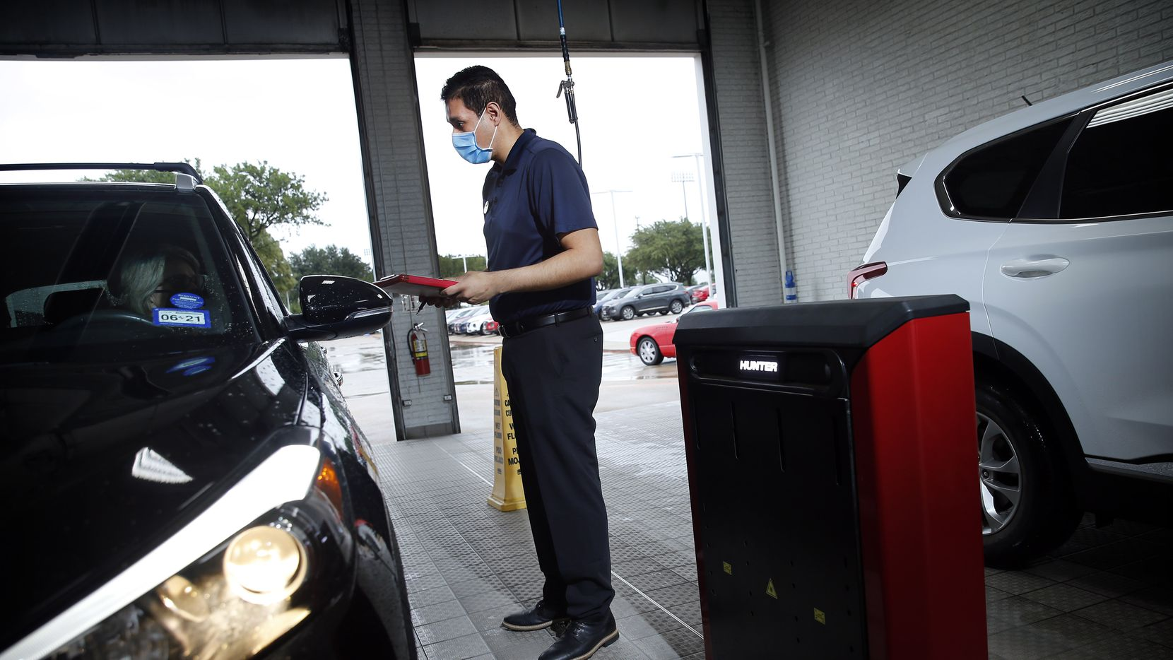 Service technician Eric Alejandraz check with a car owner about getting service at Huffines Hyundai in Plano on Sept. 2.