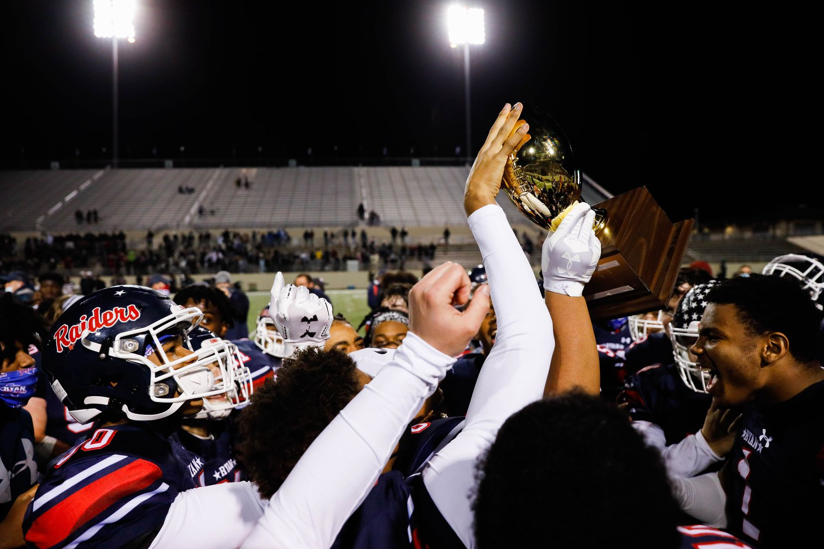 Denton Ryan football players celebrate winning the District 5-5A Division I title against Frisco Lone Star at the C.H. Collins Complex in Denton on Thursday, Dec. 4, 2020. Denton Ryan won, 35-21. (Juan Figueroa/ The Dallas Morning News)