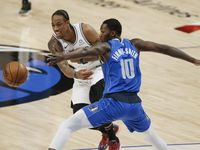 San Antonio Spurs forward DeMar DeRozan, left, passes as Dallas Mavericks forward Dorian Finney-Smith (10) defends during the first half of an NBA basketball game in Dallas, Sunday, April 11, 2021.