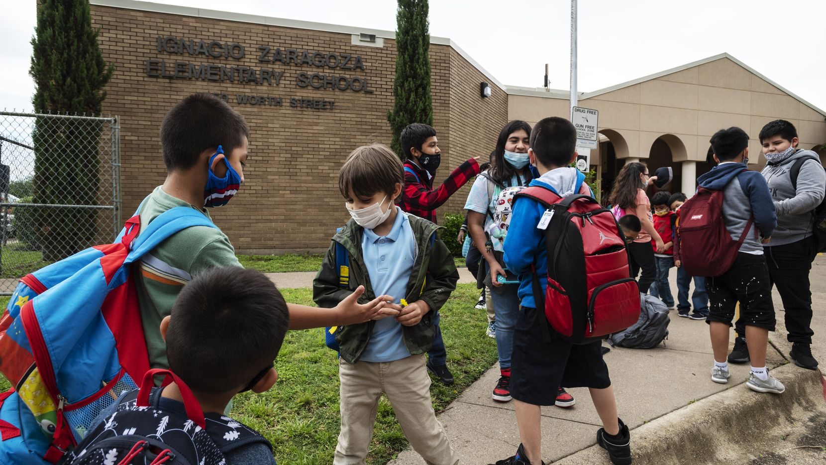 A group of students wearing face masks play outside of Ignacio Zaragoza Elementary School as they wait to be picked-up from school, on Tuesday, May 18, 2021 in Dallas.