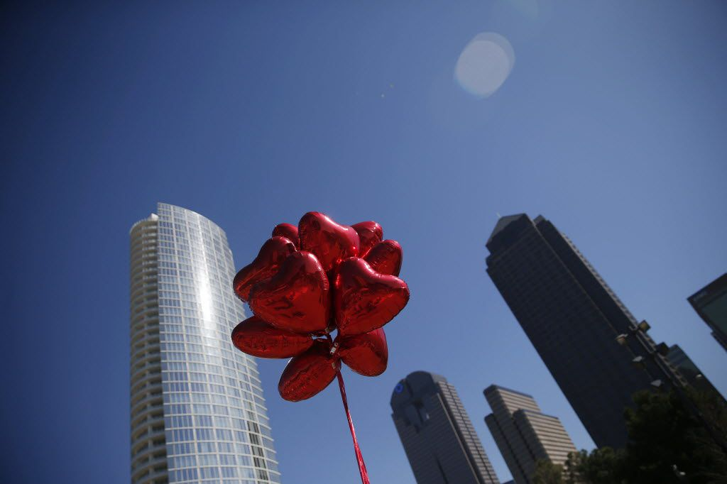 """File photo of heart-shaped balloons fly overhead during a """"Hearts in the Park"""" event at Klyde Warren Park in downtown Dallas."""