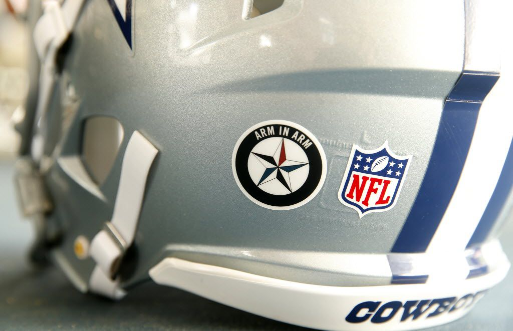 The Dallas Cowboys players are wearing a special Arm-in-Arm decal on their helmets during training camp. The decal represents the moment when Dallas police Chief David Brown joined Mayor Mike Rawlings along with the players and salon officers family members walked arm-in-arm onto the field for the opening day of training camp in Oxnard, California, Saturday, July 30, 2016. (Tom Fox/The Dallas Morning News)