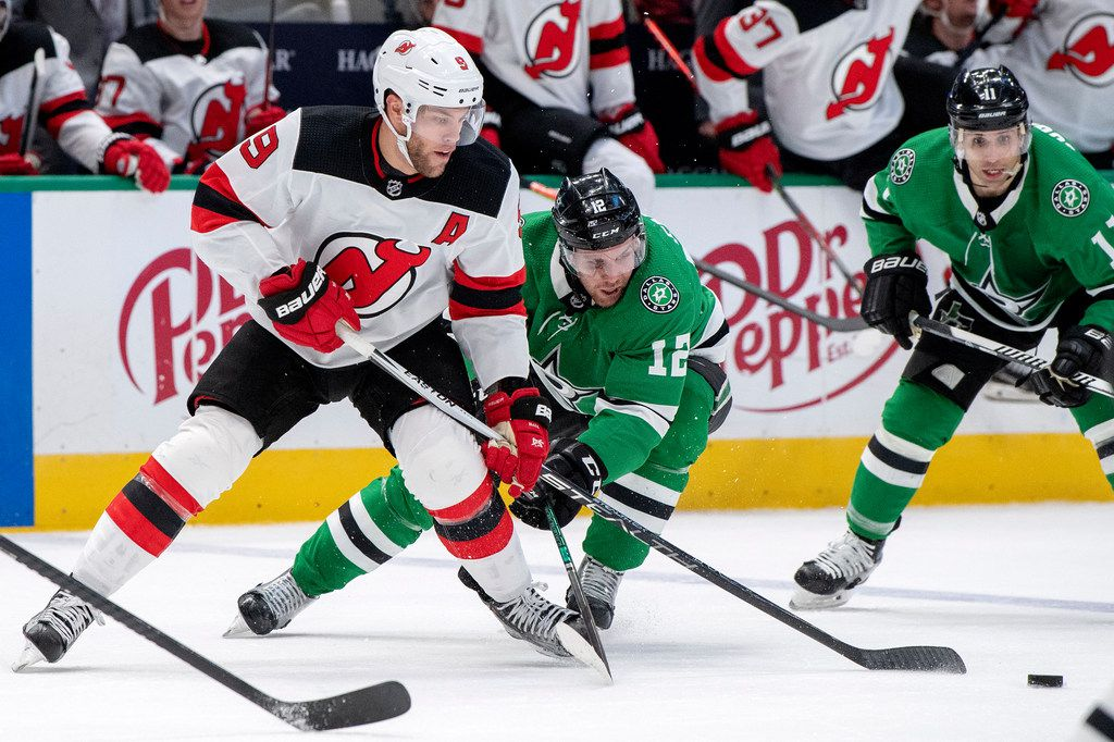 New Jersey Devils left wing Taylor Hall (9) and Dallas Stars center Radek Faksa (12) compete for the puck in the second period of an NHL hockey game, Tuesday, Dec. 10, 2019, in Dallas. Dallas won 2-0. (AP Photo/Jeffrey McWhorter)
