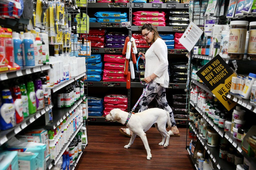 "Mackenzie Capetillo, of Dallas, walks toward the back of the store to bathe her dog, Zoey, while visiting Hollywood Feed with her mother, Suzanne Capetillo, in Dallas June 17, 2016. The store, near the corner of Royal Lane and Preston Road, opened nearly two years ago. The store advertises itself as a ""source for high quality, natural and holistic pet food and supplies."" (Andy Jacobsohn/The Dallas Morning News)"