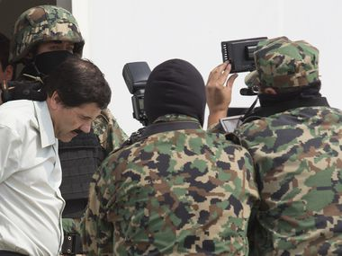"Drug trafficker Joaquin ""El Chapo"" Guzman is escorted to a helicopter by Mexican security forces at Mexico's International Airport in Mexico city, Mexico, on Saturday, Feb. 22, 2014. Mexico's apprehension of the world's most-wanted drug boss struck a blow to a cartel that local and U.S. authorities say swelled into a multinational empire, fueling killings around the world."