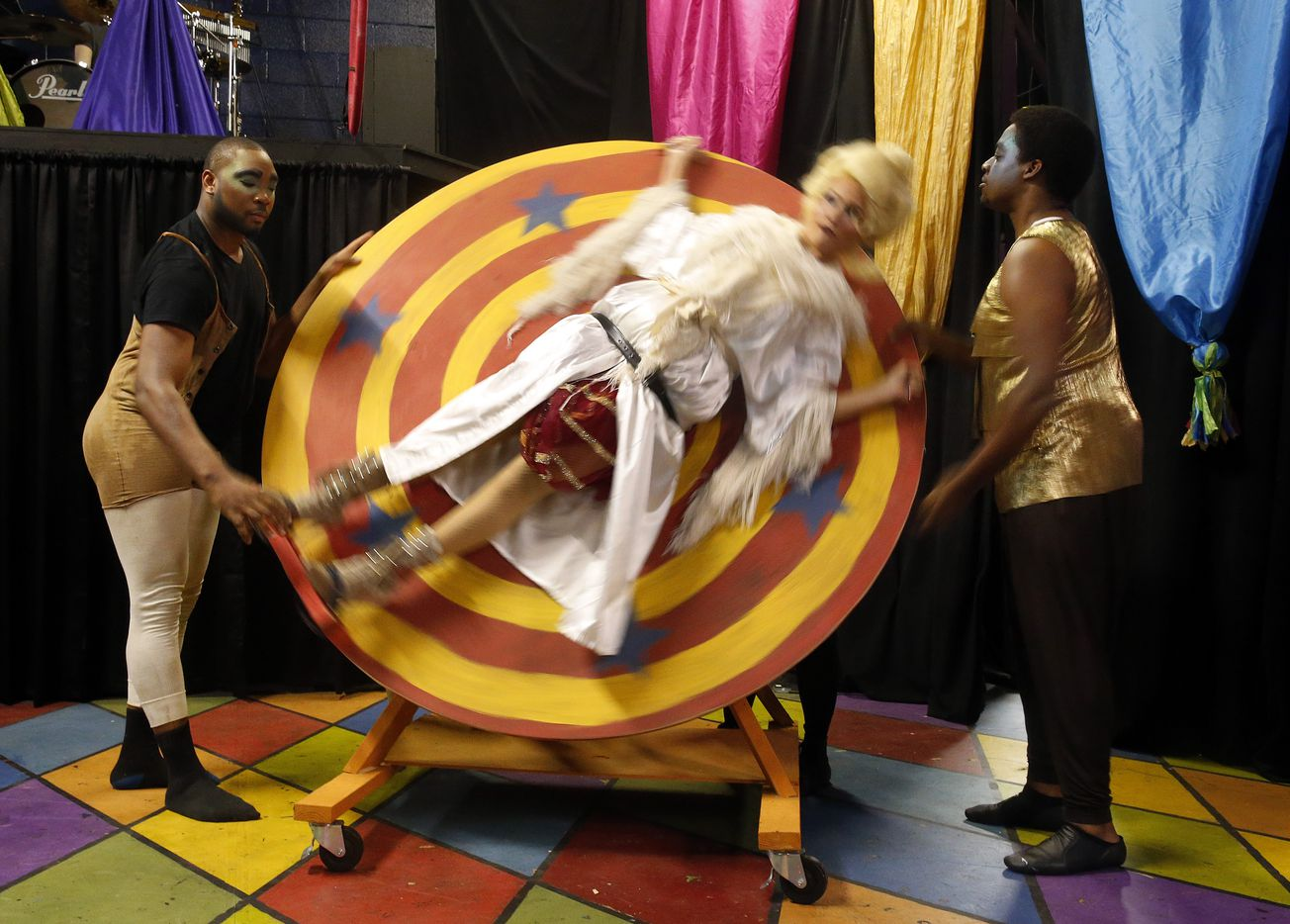 Kim Borge Swarner (Fastrada) is spun on a wheel by actors Rodney M. Morris (left) and Ania Lyons as they tested the wheel and the knife-throwing during the Pippin dress rehearsal.