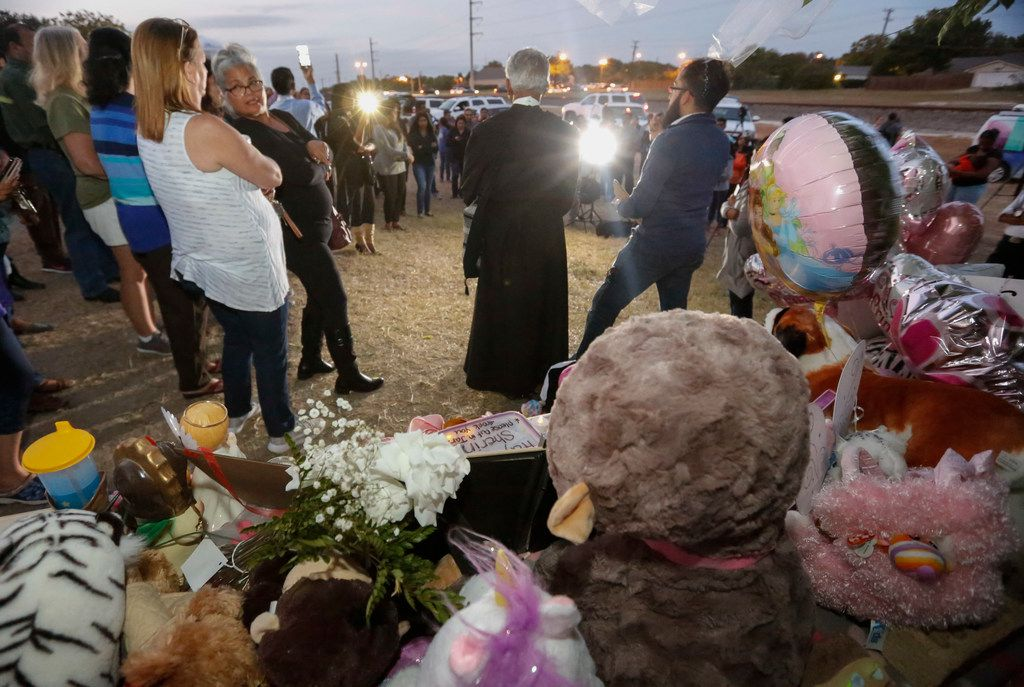 Stuff animals left for Sherin Mathews form the backdrop for a vigil held for the three-year-old girl in Richardson, Texas Friday night, October 20, 2017. The vigil was held in an alley by a tree near her parents house where her father said her left her on October 7, 2017.