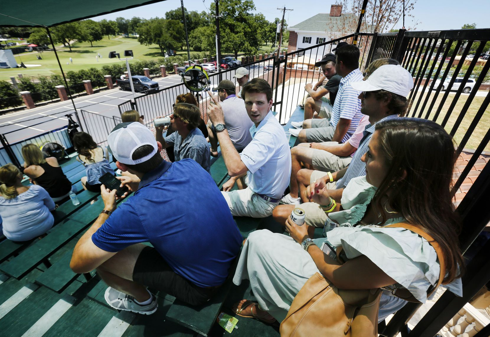 Jeff Wilhelm (center) turns to visit with Maddy Conklin (right) as they watched the third round of the Charles Schwab Challenge. Their view of the 15th green and 16th tee box are from grandstands built behind Pat Henggeler's home next to the Colonial Country Club in Fort Worth, Saturday, June 13, 2020. Last year they all went to the course to watch the action.