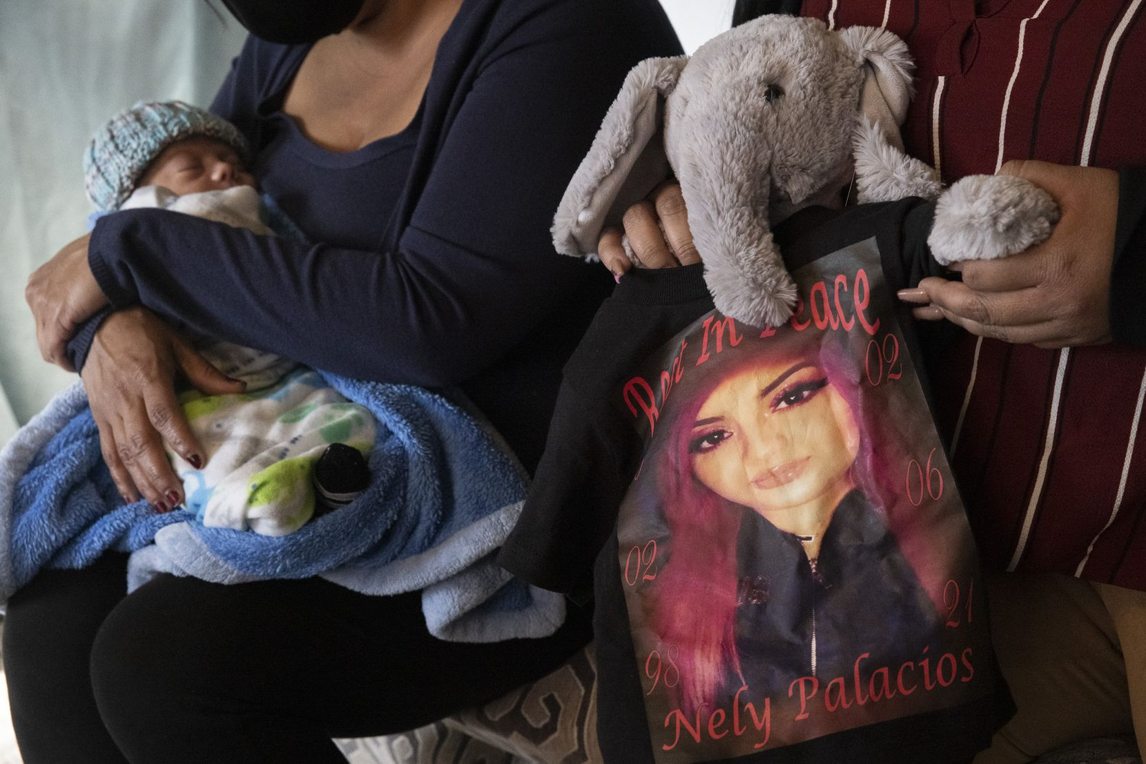 Lucy Palacios holds a stuffed elephant clad in a small version of the T-shirts created to honor her sister, Nely. At Lucy's side is Miriam with Isaiah. The stuffed elephant, given to the family by the Parkland NICU, contains a toy heart that plays a recording of Nely's own heartbeat.