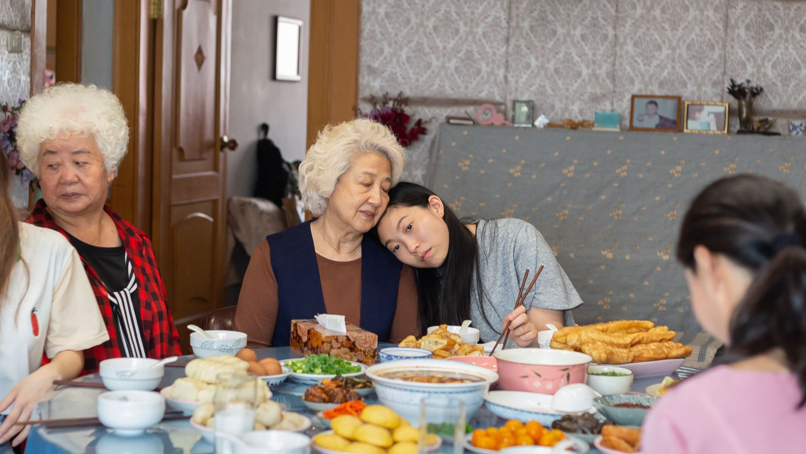 Billi (right, Awkwafina) shares an intimate moment with Nai Nai (Zhao Shuzhen) in a breakfast scene from The Farewell.