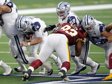 On fourth-and-1, Cowboys quarterback Andy Dalton (14) squeezes through for a first down against Washington in the second quarter at AT&T Stadium in Arlington on Thursday, Nov. 26, 2020.