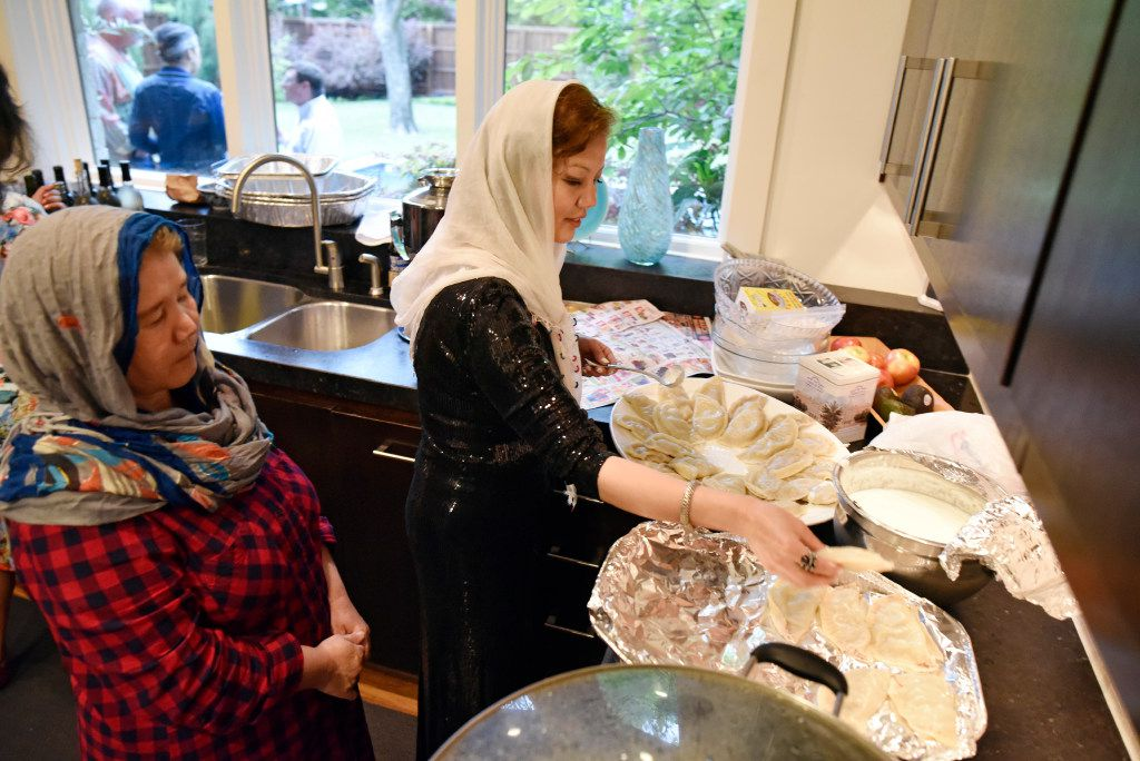 Sharifeh Hasani (left) watches her sister, Jamileh Jafari, prepare beef dumplings known as mantu during an Afghan-style dinner.