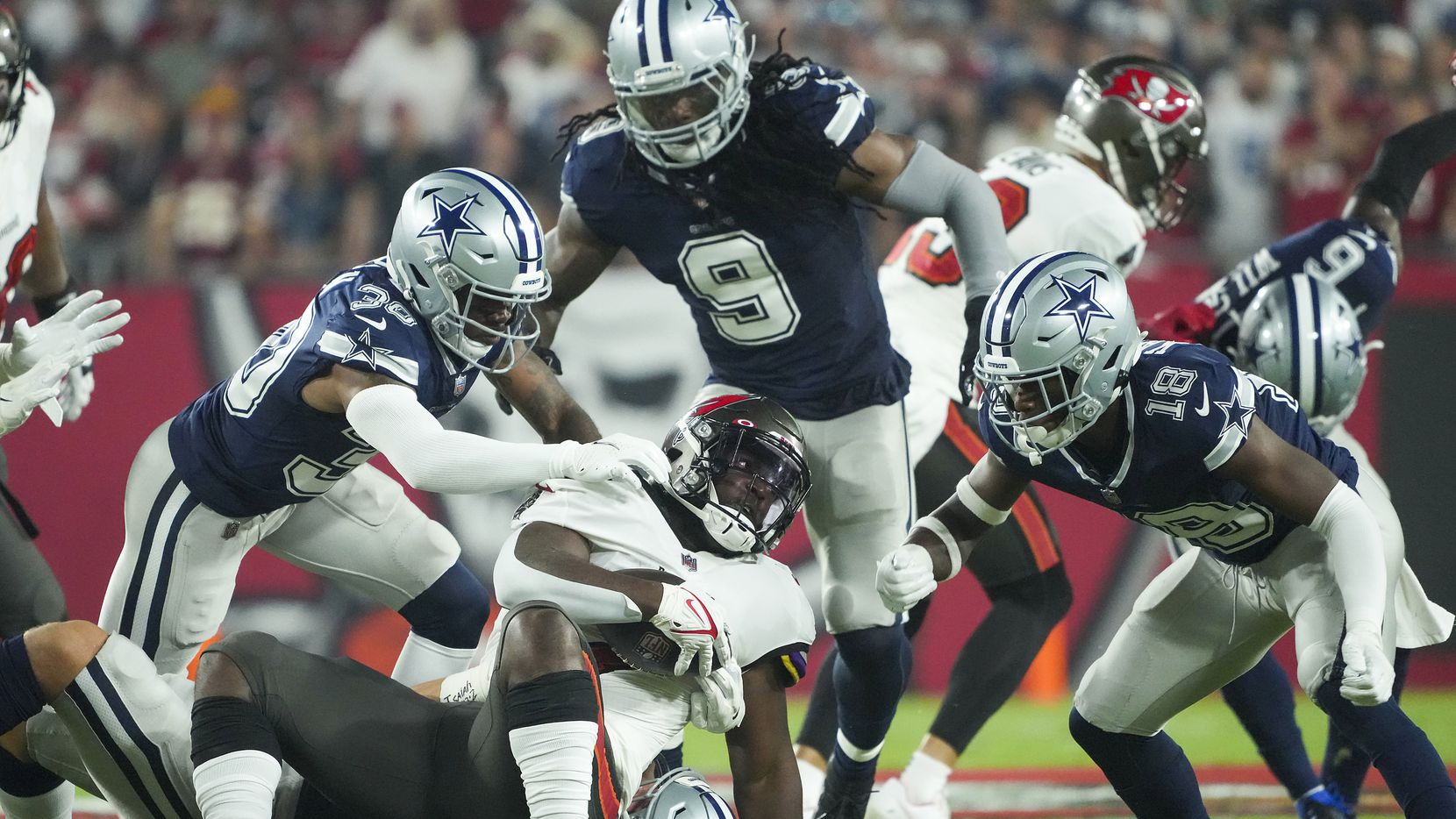 Tampa Bay Buccaneers running back Leonard Fournette (7) is brought down by Dallas Cowboys linebacker Leighton Vander Esch (55) along with cornerback Anthony Brown (30), linebacker Jaylon Smith (9) and safety Damontae Kazee (18) during the first half of an NFL football game at Raymond James Stadium on Thursday, Sept. 9, 2021, in Tampa, Fla.