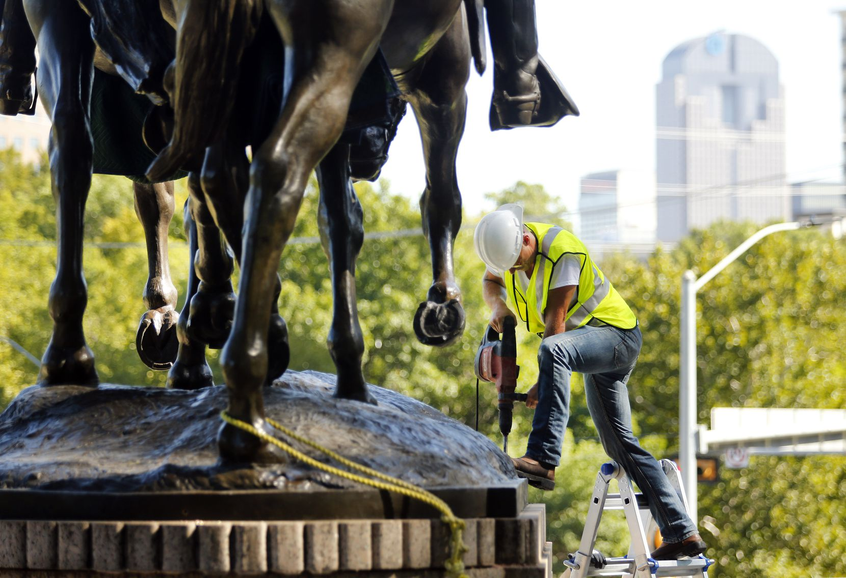 A crewman from Howell Crane and Rigging Inc. drills into the base of the statue has they had trouble removing it.