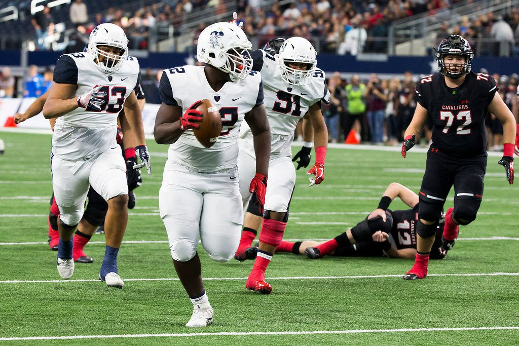 Allen defensive lineman Jayden Jernigan (42) recovers a fumble by Lake Travis quarterback Matthew Baldwin (12), who collapses to the turf grabbing his injured right knee, and runs it in for a touchdown during the first half of the Class 6A Division I state championship game at AT&T Stadium on Saturday, Dec. 23, 2017, in Arlington, Texas. (Smiley N. Pool/The Dallas Morning News)