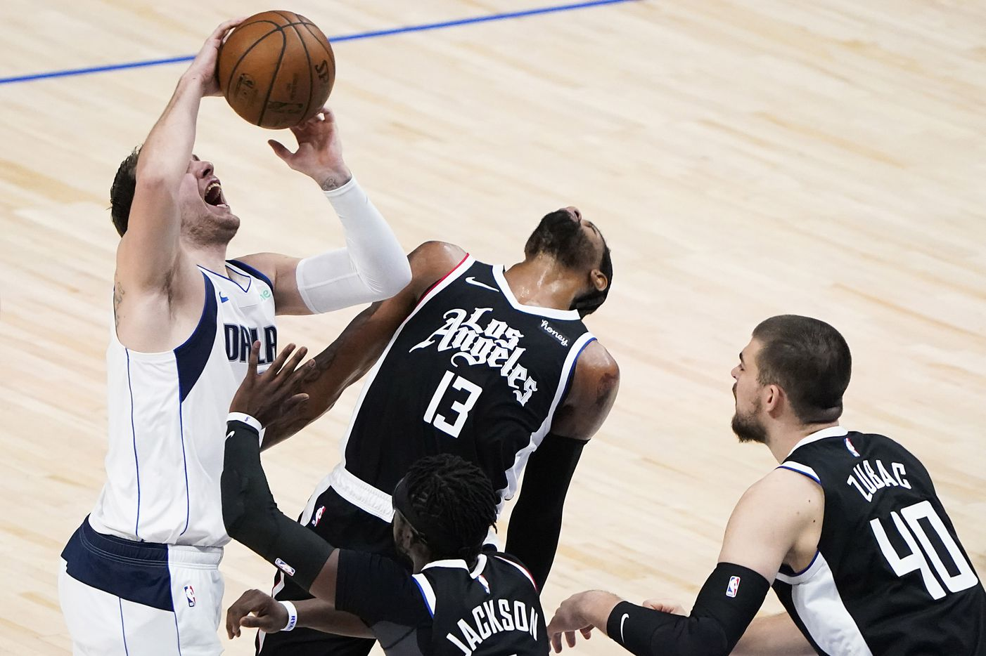 Dallas Mavericks guard Luka Doncic (77) loses the ball as LA Clippers guard Paul George (13) and guard Reggie Jackson (1) defend during the first quarter of an NBA playoff basketball game at American Airlines Center on Sunday, May 30, 2021, in Dallas.