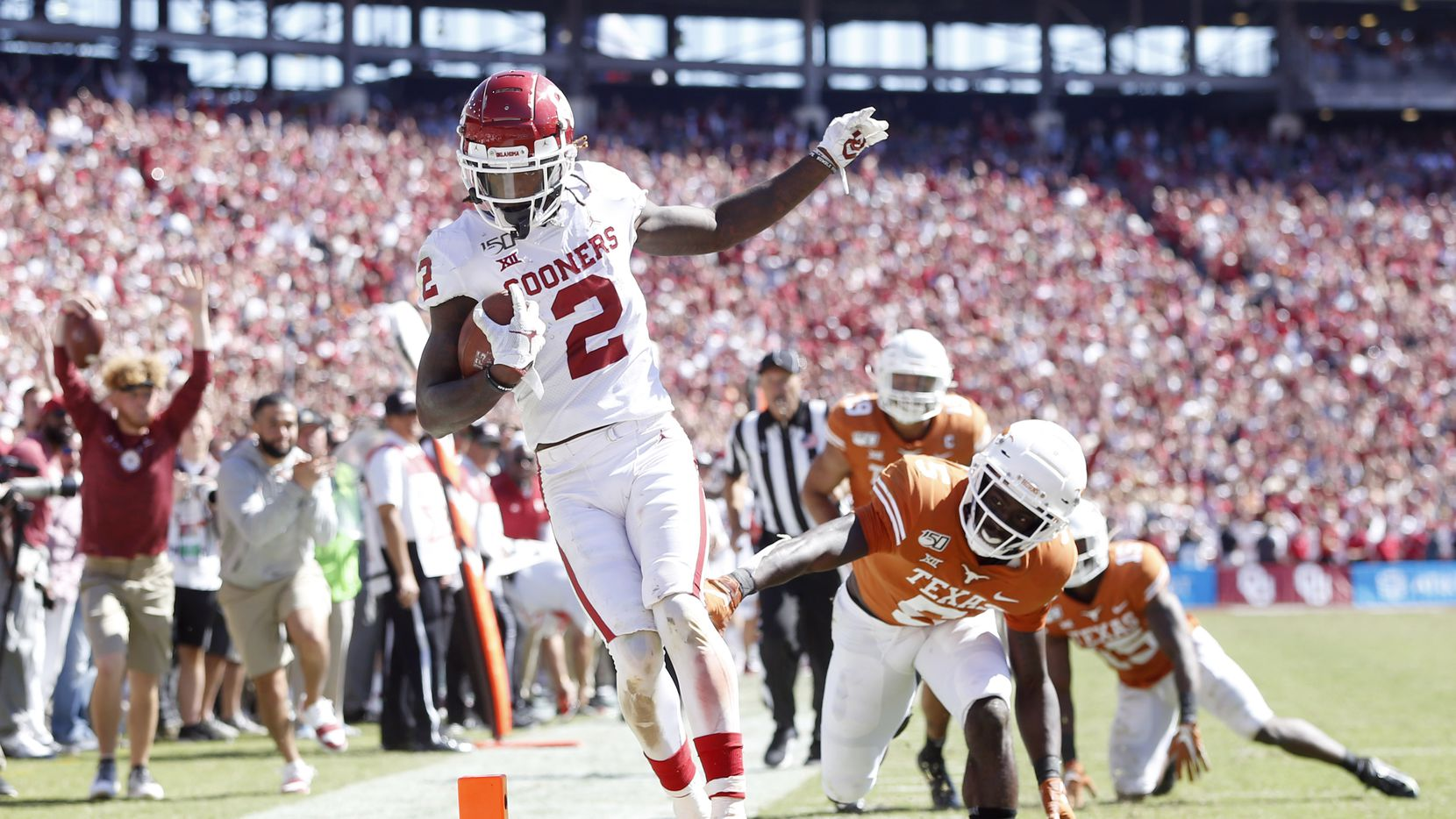 FILE - Oklahoma wide receiver CeeDee Lamb (2) scores a touchdown after beating Texas defensive back D'Shawn Jamison (5) during the second half of the Red River Showdown at the Cotton Bowl in Dallas on Saturday, Oct. 12, 2019.
