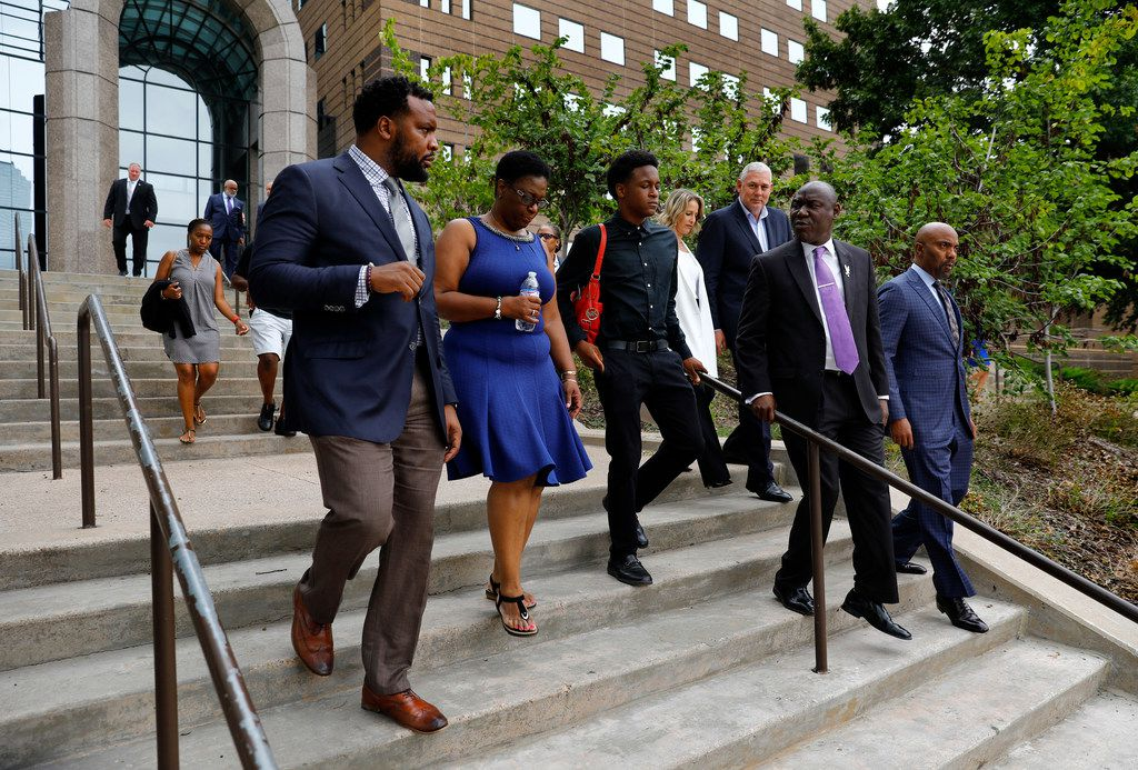 (from left) Attorney Lee Merritt, Allison Jean, mother of shooting victim Botham Jean, her son Brandt Jean and attorney Benjamin Crump descend the stairs outside the Frank Crowley Courts Building for a family press conference, Monday, September 10, 2018. Botham Jean was shot and killed by Dallas police officer Amber Guyger in his own apartment last week.  (Tom Fox/The Dallas Morning News)