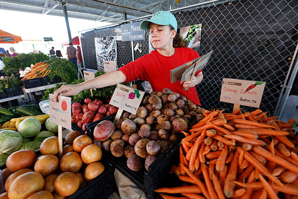 Josslyn Julka, 12, with Market Provisions places signs in each of the items offered for sale in The Shed at the Dallas Farmers Market. The signs show the buyer where each item was grown.