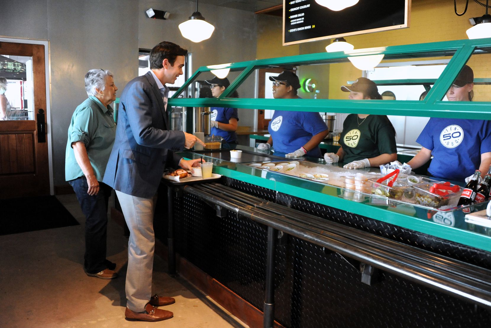Guests order sides in the buffet style line at the new Ten 50 BBQ in Richardson.