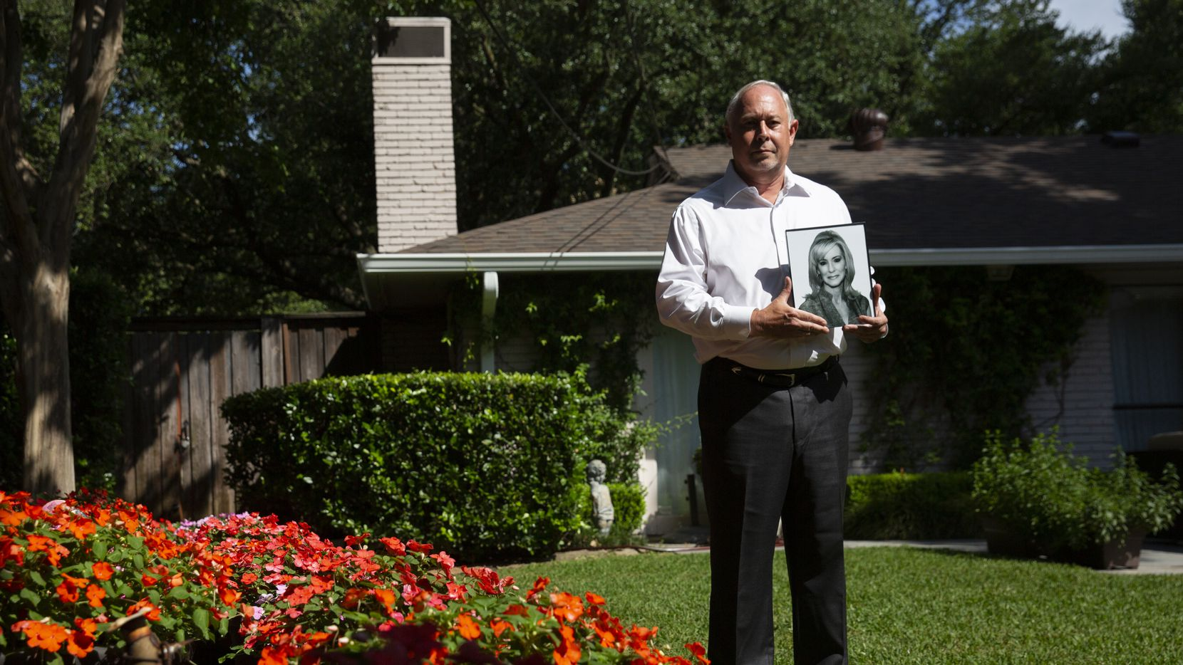 "Robert Baker holds a photo of his wife, Leslie Squair Baker, in the backyard of his North Dallas home. ""She is everything you have read,"" he said of her. ""She cared about people. She didn't care where they came from."""