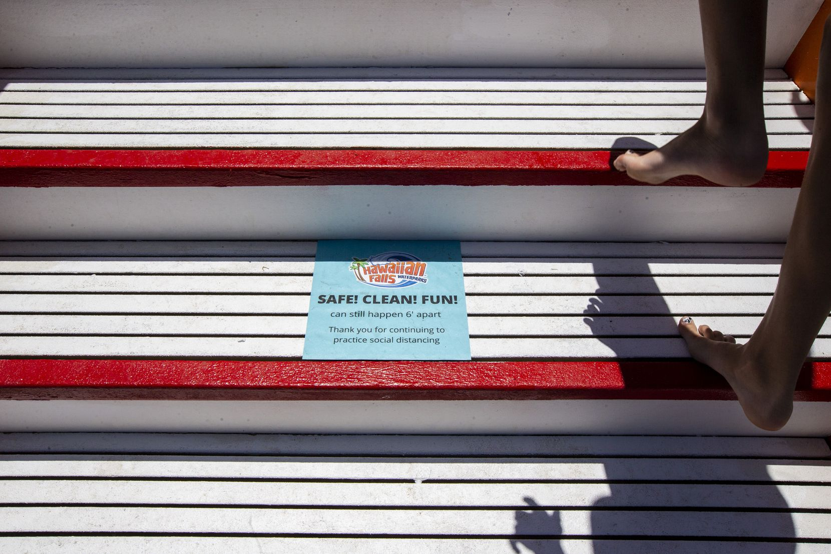 Social distancing reminders line the staircase as customers climb up to a water attraction at Hawaiian Falls.
