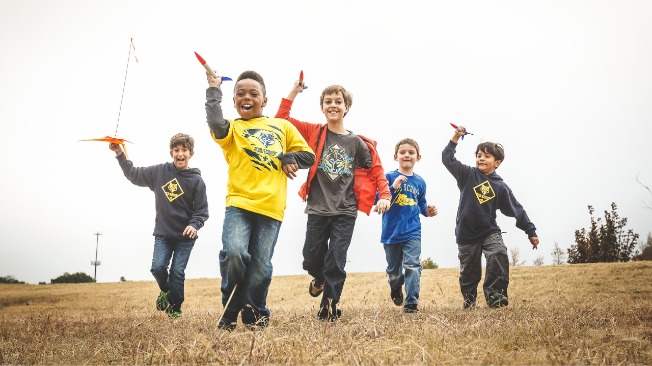 A group of young scouts runs through a field with toy rockets.