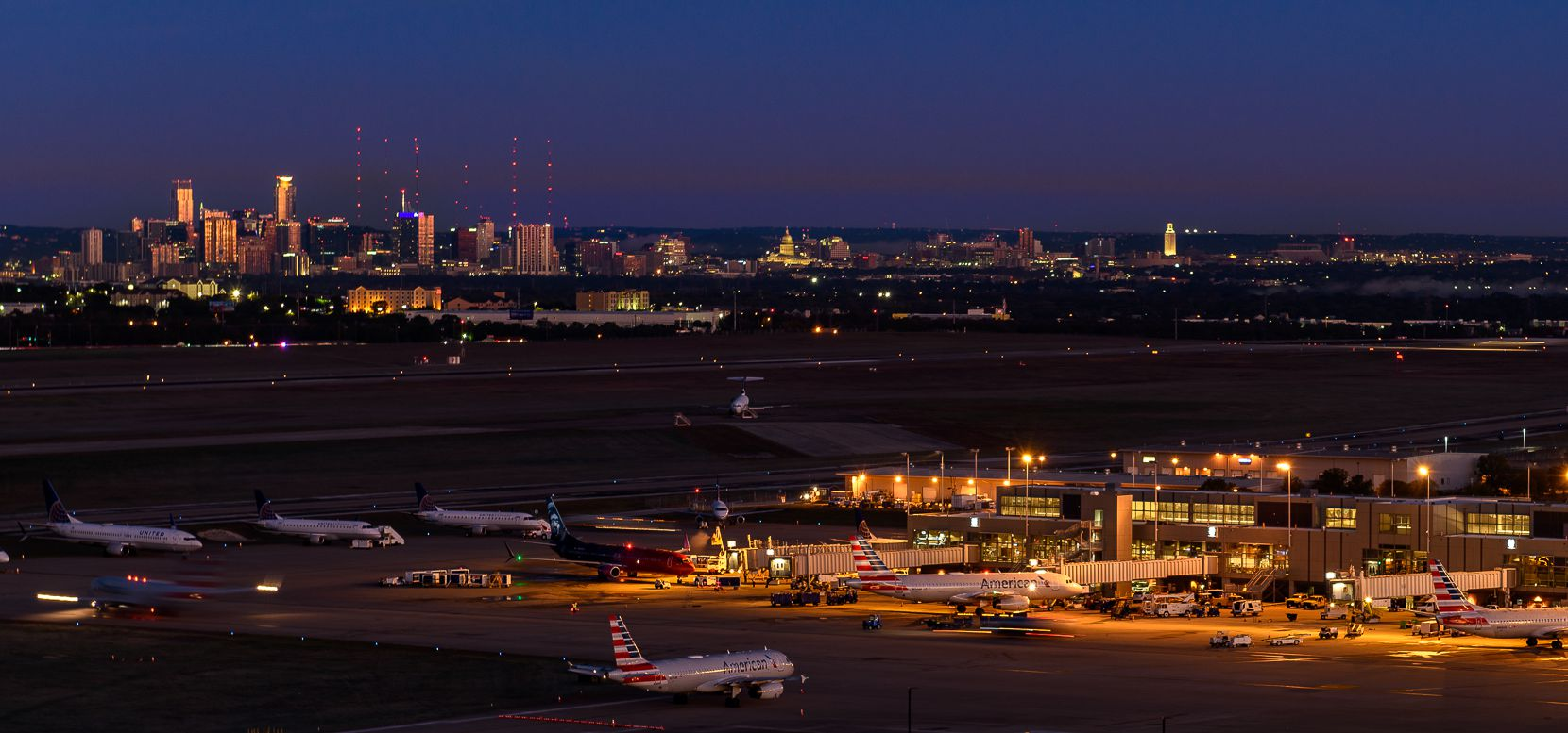 A nighttime view of Austin-Bergstrom International Airport with the city of Austin in the distance.