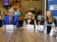 Texas Gov. Greg Abbott (left) listens to a question from Roberts Trucking CEO Quincy Roberts (right) during a roundtable with small business owners at the Dallas Farmers Market on Friday.