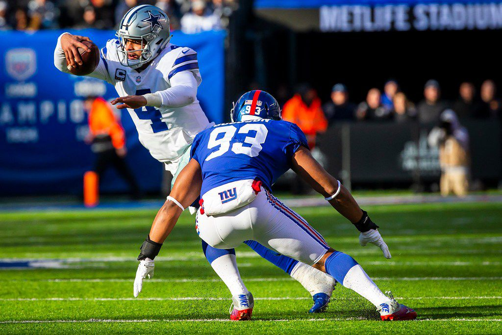 Dallas Cowboys quarterback Dak Prescott (4) scrambles away from New York Giants middle linebacker B.J. Goodson (93) during the first half of an NFL football game at MetLife Stadium on Sunday, Dec. 30, 2018, in East Rutherford, New Jersey.