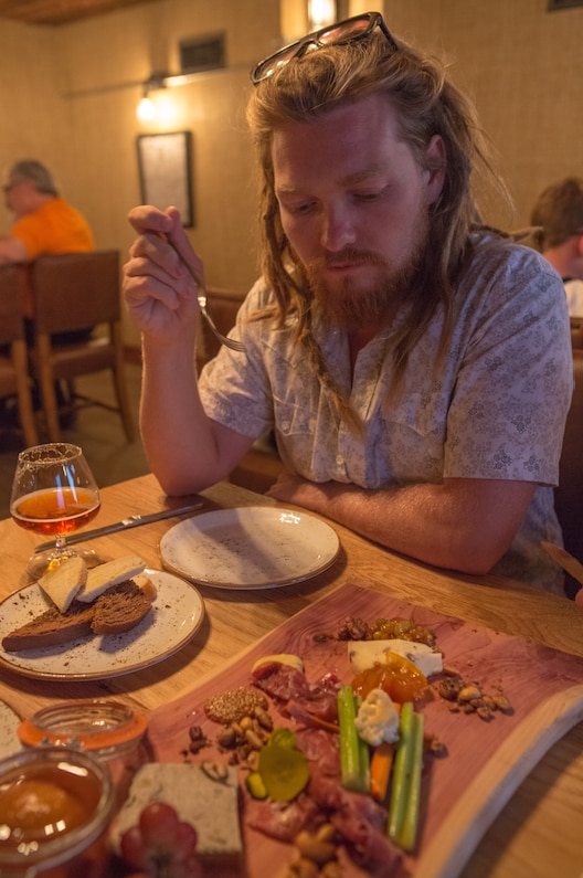 Local businessman Matt Arnold enjoys The Motherboard, a collection of chef favorite items from the menu served on one of the signature boards, at Barley and Board's soft opening event on Tuesday, August 11, 2015 in Denton, Texas.