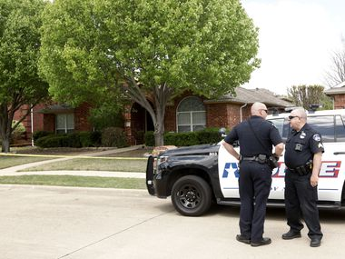 Police stand outside a home in Allen where six people were found dead Monday.