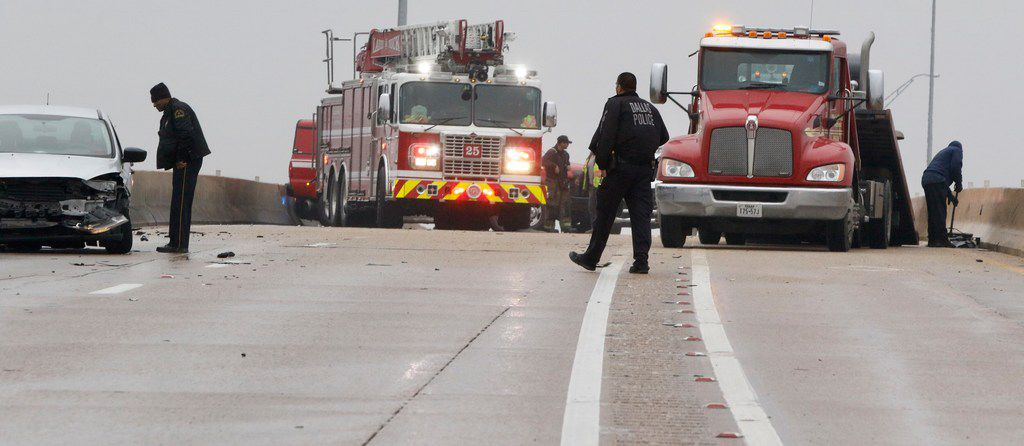 Dallas Police officers work an accident on southbound Hwy. 67 over Hampton Road on February 28, 2019 in Dallas. Freezing temperature and wet conditions overnight led to icy roads, causing dozens of accidents.