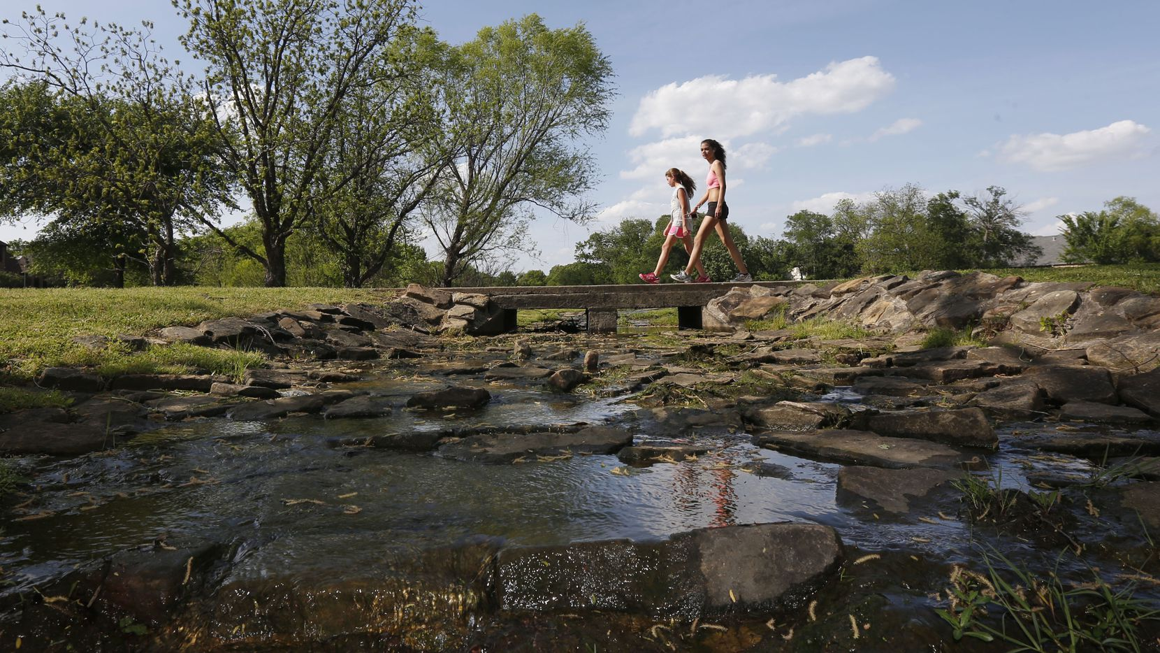 Two unidentified girls walk over a creek at the Colleyville Nature Center on April 23, 2014.  (Michael Ainsworth/The Dallas Morning News)