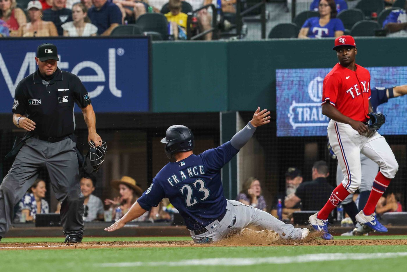 Seattle Mariners Ty France (23)slides home safely scoring  run 8 for the team against Texas Rangers in the seventh inning at Globe Life Field in Arlington, Texas, Friday, July 30, 2021. (Lola Gomez/The Dallas Morning News)