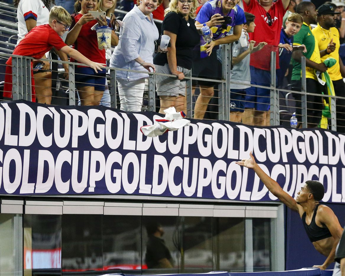USA defender Reggie Cannon (2) tosses his jersey to a young fan after a CONCACAF Gold Cup quarterfinal soccer match against Jamaica at AT&T Stadium on Sunday, July 25, 2021, in Arlington. (Elias Valverde II/The Dallas Morning News)