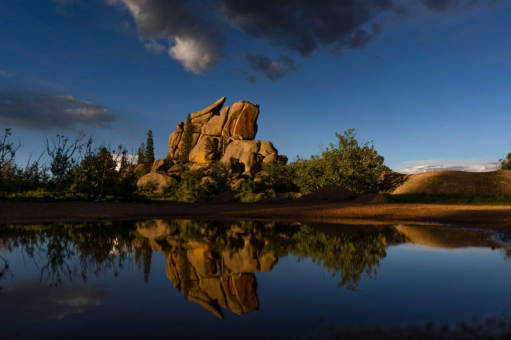 Rock formations are reflected in water after a storm near Vedauwoo Recreation Area near Cheyenne, Wyo.
