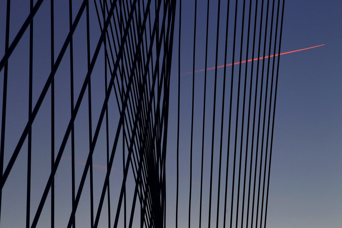 The contrail of a jet appears pink in the light of the setting sun, juxtaposed against the pattern of high tension cables of the Margaret Hunt Hill Bridge, January 20, 2012.  World-renowned architect Santiago Calatrava designed the bridge spanning the Trinity River between downtown and West Dallas. (Tom Fox/The Dallas Morning News)