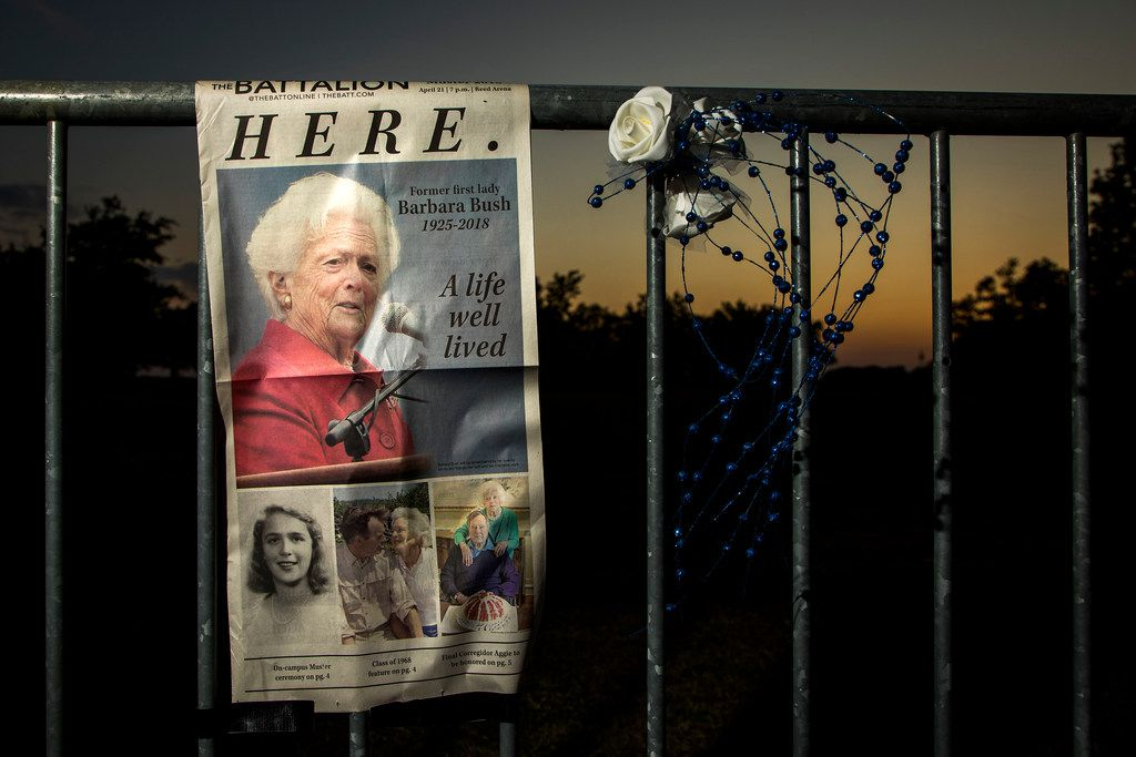 A page from The Battalion student newspaper hangs from a fence at a memorial to former first lady Barbara Bush as the sun sets near her husband's presidential library at Texas A&M University on Friday, April 20, 2018, in College Station.