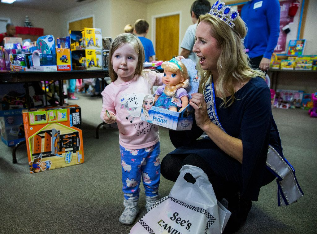 Victoria Carpenter, 3, shows her baby doll to Mrs. Texas Kim Bader during The Big Christmas Do-Over on December 17 at First Baptist Church in Rowlett. Donated toys, Christmas decorations and food were distributed to families who were effected by the tornado that ripped through the area on Dec. 26, 2015.