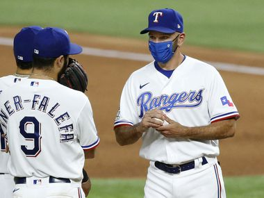 FILE — Texas Rangers manager Chris Woodward (right) visits with shortstop Isiah Kiner-Falefa (9) on the mound after pulling relief pitcher Juan Nicasio (40) during the eighth inning at Globe Life Field in Arlington, Monday, August 17, 2020. Woodward was suspended by the league for a game. Nicasio gave up a grand slam to San Diego Padres Fernando Tatis Jr.