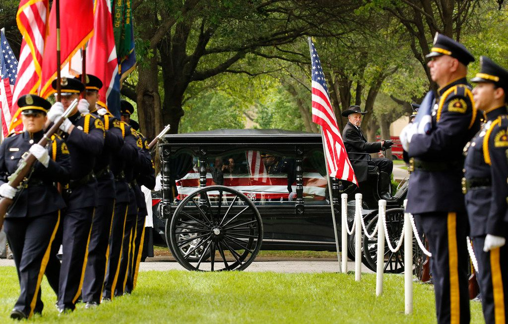 The Dallas Police Color Guard (left) enters the Garden of Honor as it escorted the horse-drawn carriage carrying officer Rogelio Santander to his resting place at Restland Memorial Park.