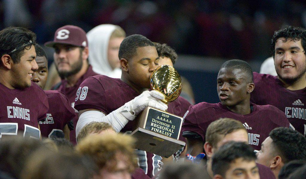 Ennis' Lazurus Becks (98) kisses the trophy after a Class 5A Division II Region  II semifinal high school football game between Frisco and Ennis, Friday, Nov. 29, 2019, in Frisco, Texas. Ennis won 17-0. (Matt Strasen/Special Contributor)