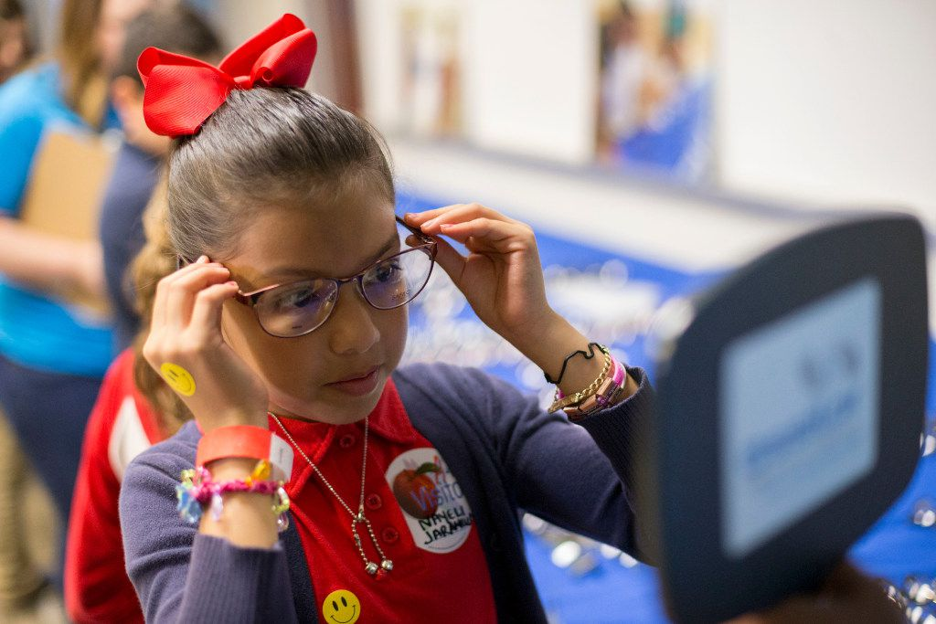 Nayeli Jaramille, 9, tries on different glass frames provided by Essilor Vision Foundation during World Sight Day at Essilor of America on Oct. 13, 2016 in Dallas, Texas.