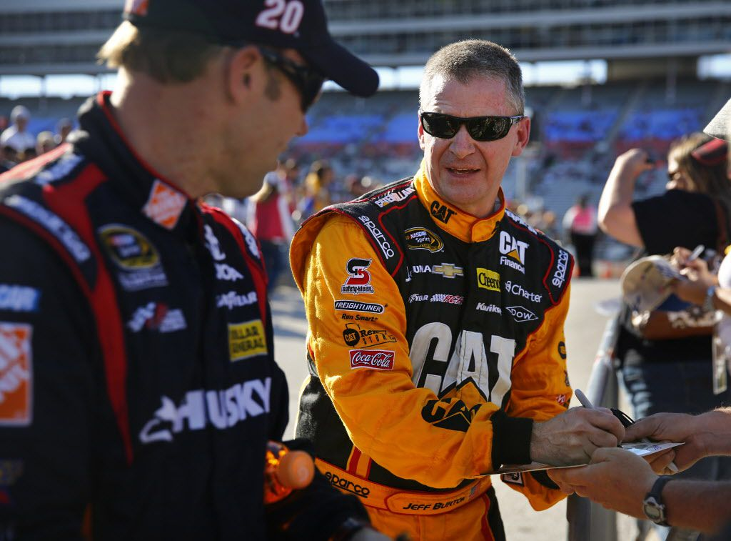 Sprint Cup Series driver Jeff Burton, center, signs autographs for fans with points leader Matt Kenseth following their qualifying runs for Sunday's  AAA Texas 500, Friday, November 1, 2013, at the Texas Motor Speedway.