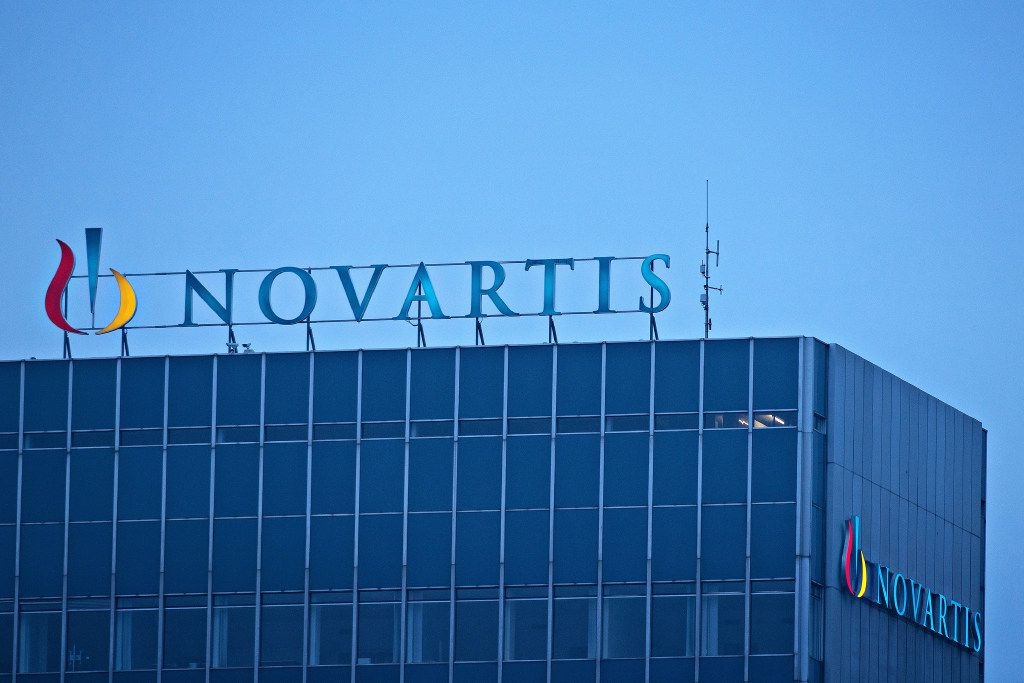 The Novartis AG Logo sits on top of the company's headquarters office in Basel, Switzerland, on Wednesday, Jan. 25, 2017. Novartis proposed buying back $5 billion of shares and said it's considering separating its embattled eye-care division after projecting that sales this year at Europe's second-biggest drugmaker will likely be largely unchanged from 2016. Photographer: Michele Limina/Bloomberg
