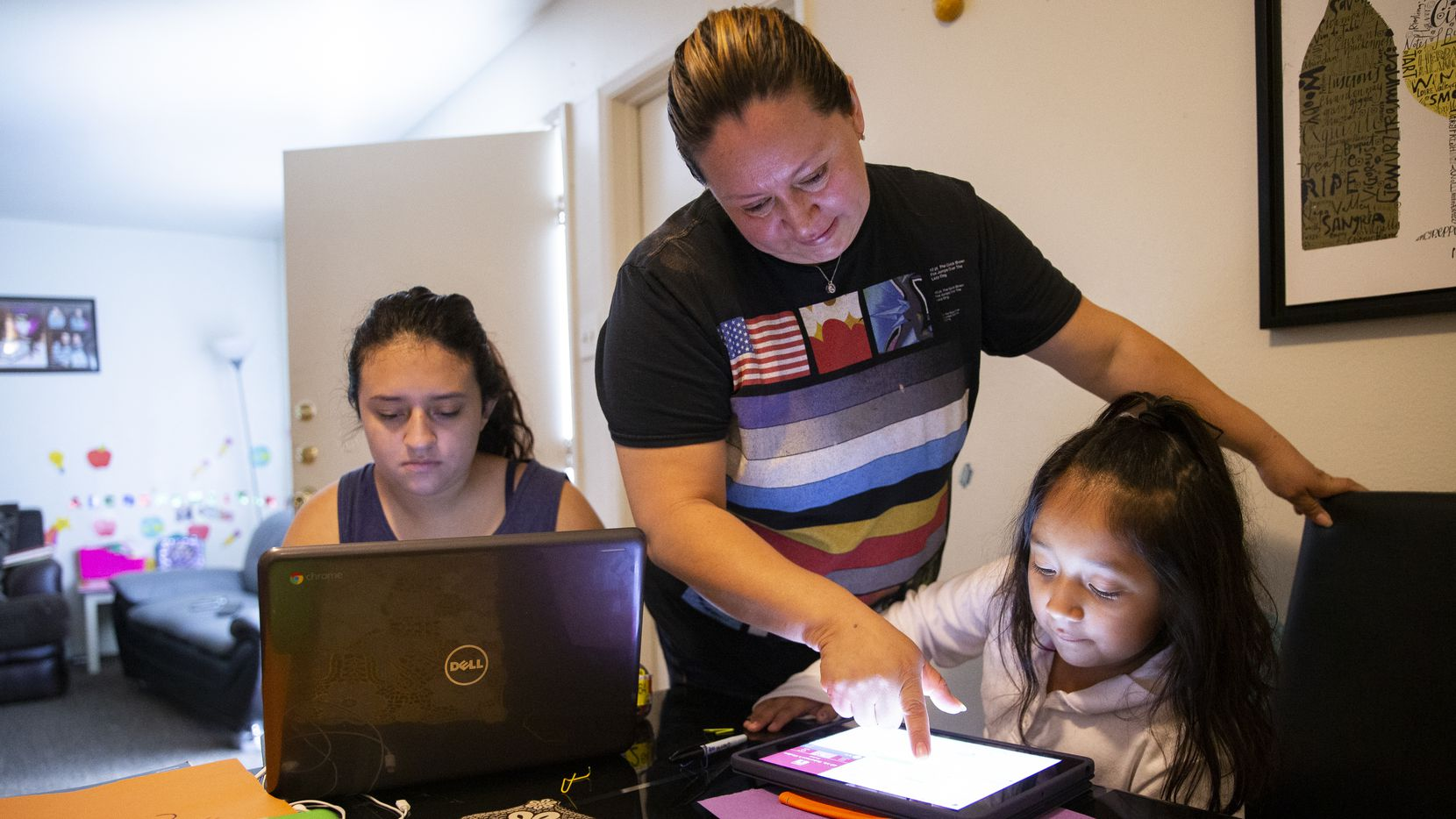 Hebreny Cojulum, 19, attends her Integrated Physics and Chemistry class while mom Adali Arriaza helps sister Daysha Cojulum, 5, upload homework at the kitchen table on Sept. 16, 2020 in Northwest Dallas. The sisters use personal cellphone hotspots to connect after experiencing issues with their DISD hotspots. Texas Senators unanimously supported a proposal on Wednesday to improve internet access throughout the state. (Juan Figueroa/ The Dallas Morning News)