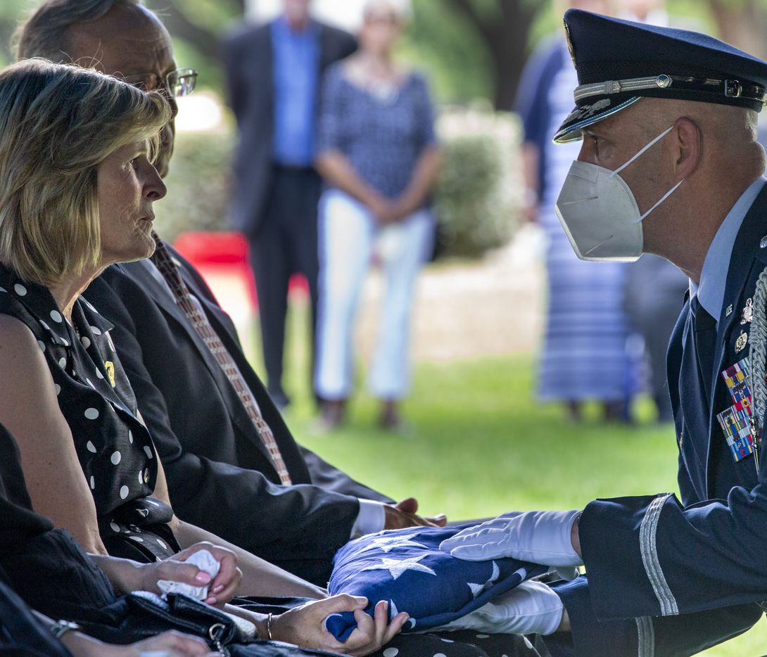 Gini Johnson Mulligan (left), daughter of Sam Johnson, receives a folded flag from a member of the Air Force Honor Guard during the funeral of her father, Congressman Samuel Robert Johnson, during his funeral at the Restland Memorial Park in Dallas on Monday, June 8, 2020. In addition to 28 years of service as a congressional representative for Texas' 3rd District, Johnson was also a fighter pilot, decorated combat veteran and a former Prisoner of War.