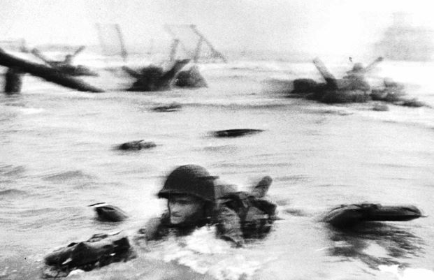 An American soldier wades through water under heavy artillery and machine-gun fire to reach the beach on the Normandy coast of France, June 6, 1944. It turned out to be the biggest and most important Allied  amphibious operation of World War II.
