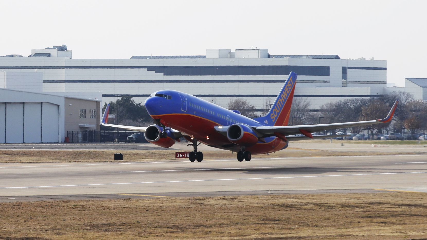 A Southwest Airlines jet takes off in front of corporate headquarters at Dallas Love Field.